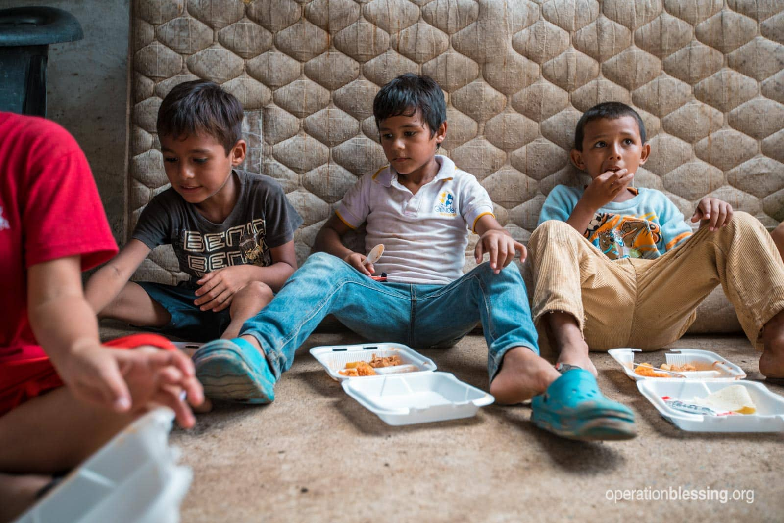 Angel and other boys eat hot meals while sitting on the floor.
