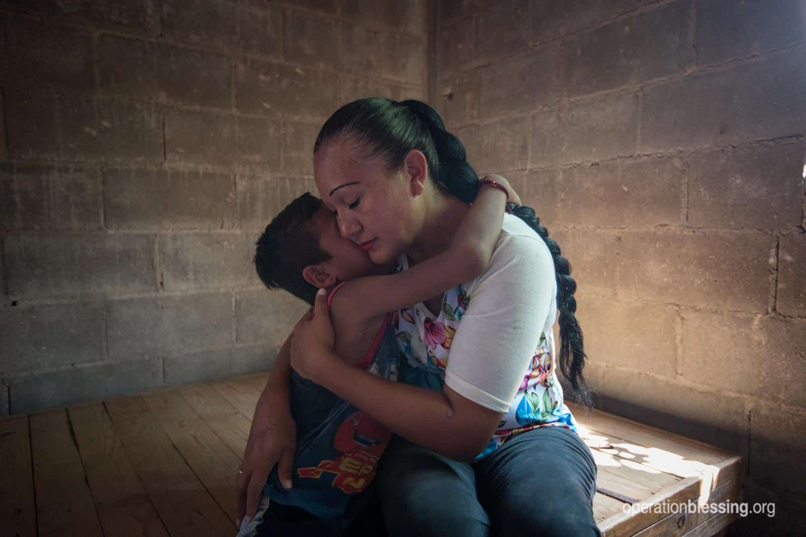 Angel's mother comforts him with a hug after they lost much in a flood in Mexico.