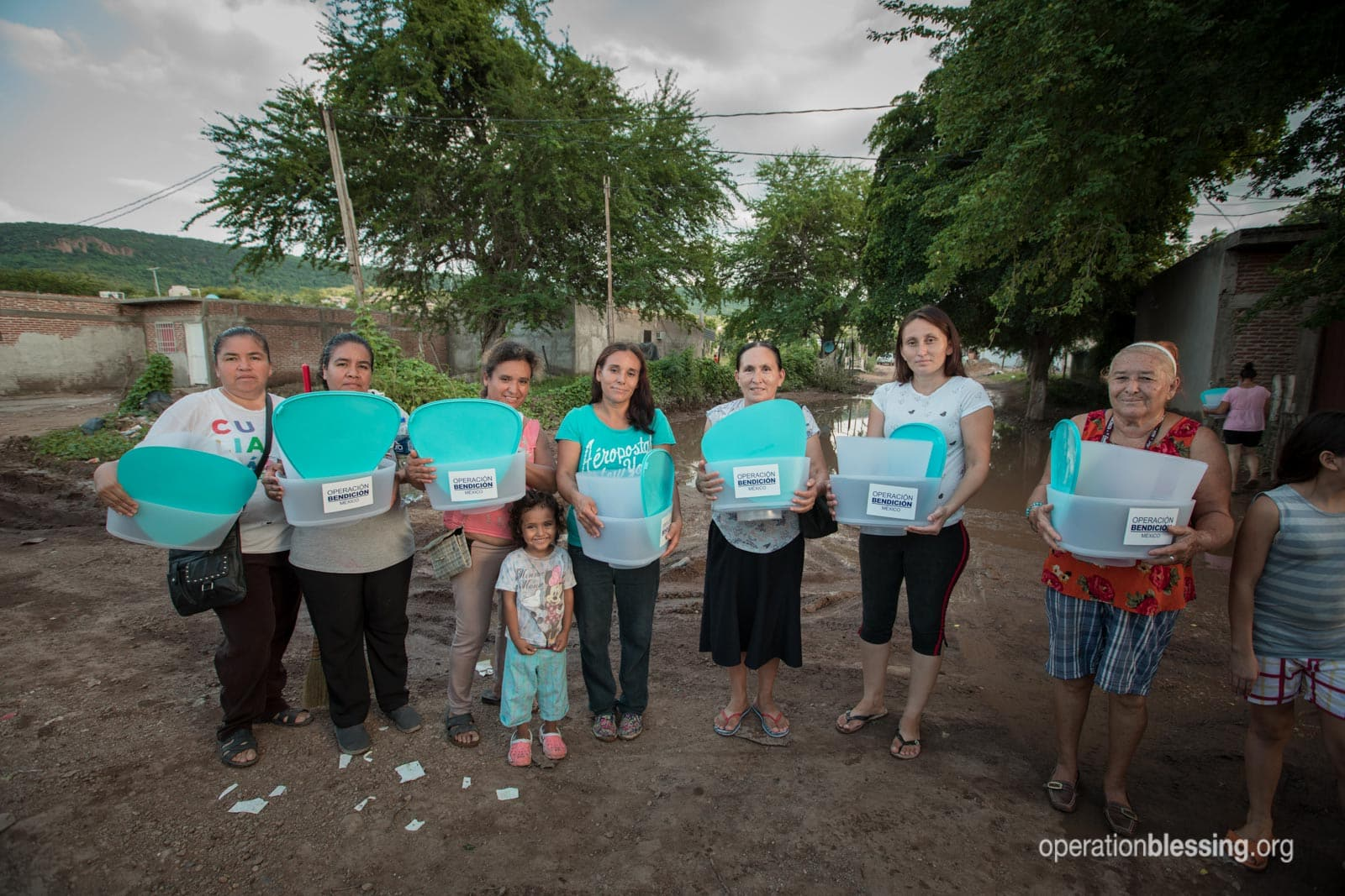 Flood victims hold Kohler Clarity filters donated by OB supporters.