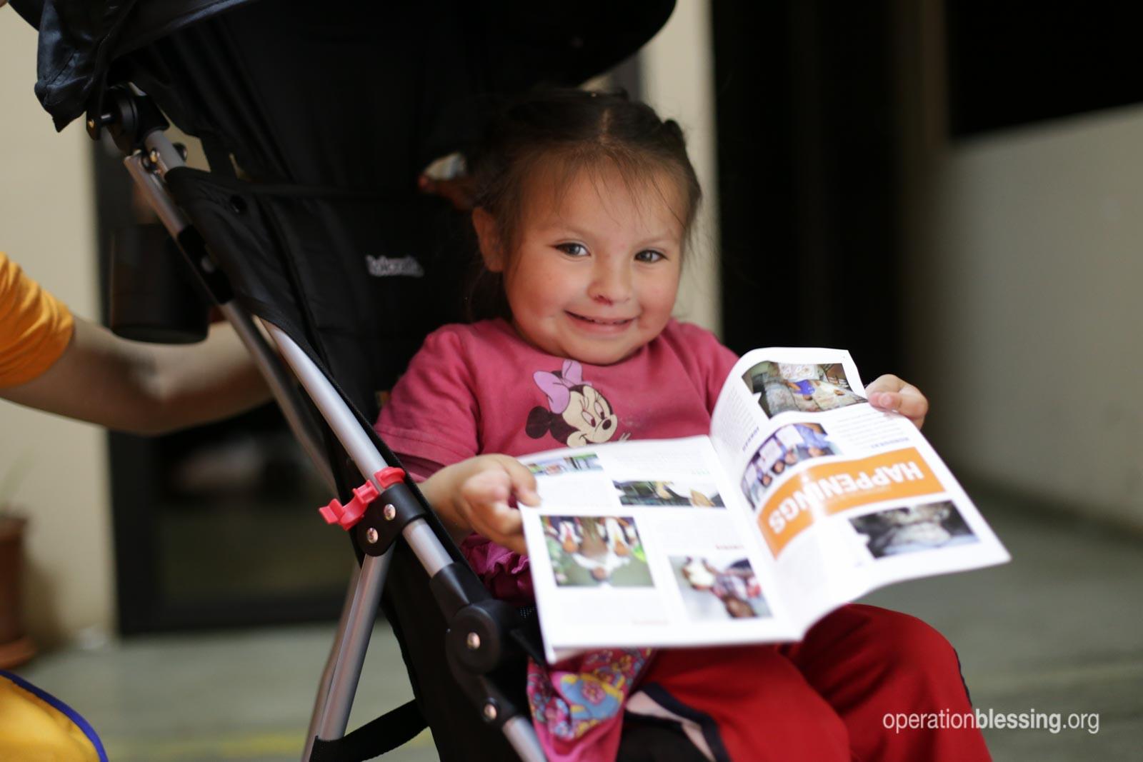 Fernanda reads Blessings magazine in her new stroller.