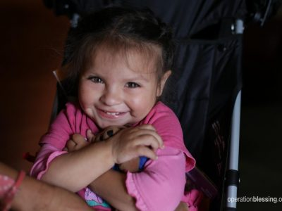 Fernanda smiles in her new stroller from Operation Blessing friends.