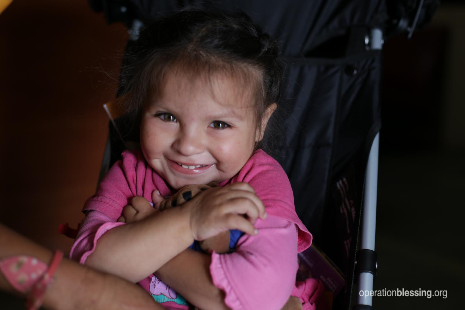Fernanda smiles in her new stroller from Operation Blessing friends.
