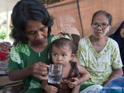 Tsunami survivor gives clean water to a baby girl.