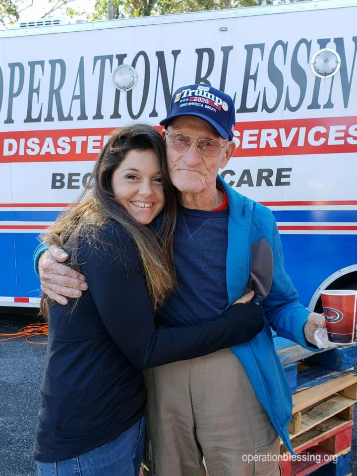 Korean War veteran hugs his granddaughter while volunteering with disaster relief for Operation Blessing.