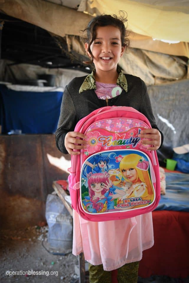 Young girl with school supplies.