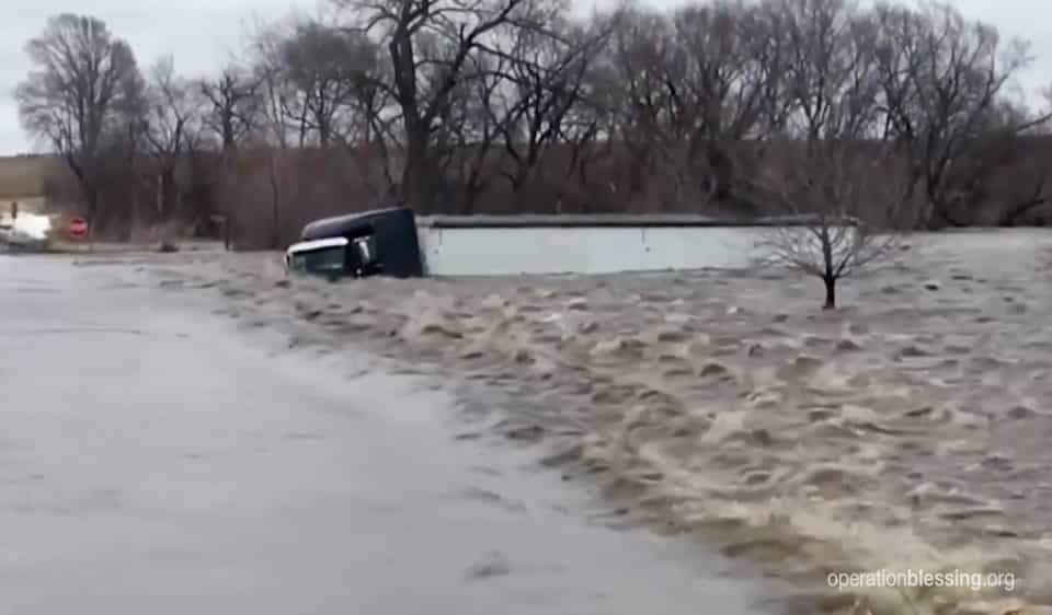 A tractor trailer is taken over by water in recent Nebraska floods