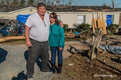 Victims of the Alabama tornadoes stand in front of their damaged home in need of disaster relief.
