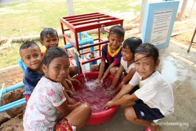 Asian children enjoy a new water well from Operation Blessing partners.