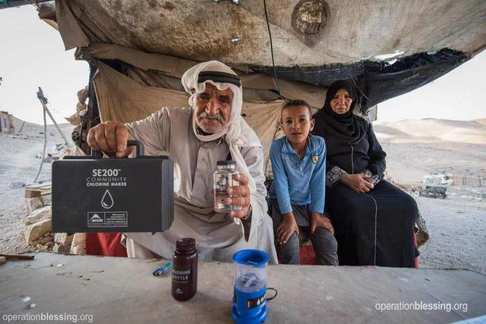 A Bedouin leader holds a chlorination device for safe water.