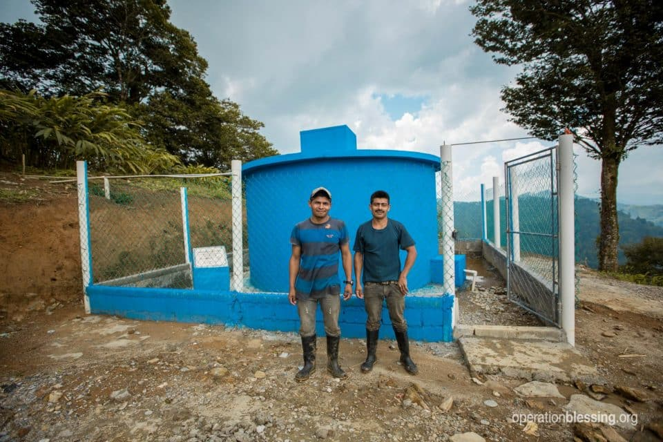 Men stand in front of water system from clean water charity, Operation Blessing.