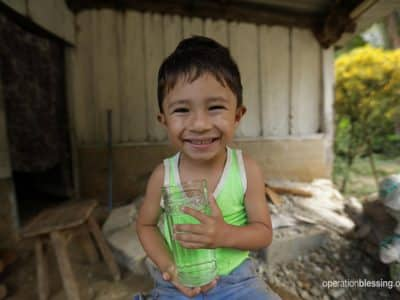 A young boy holds a water cup. Operation Blessing brings life to dry places.