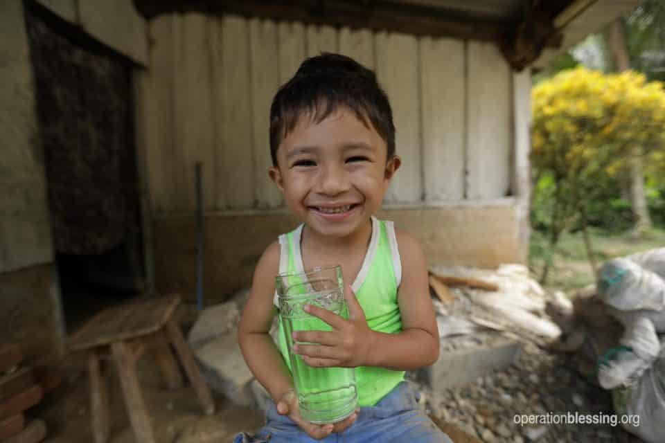 A young boy holds a cup of clean water. Operation Blessing brings life to dry places.