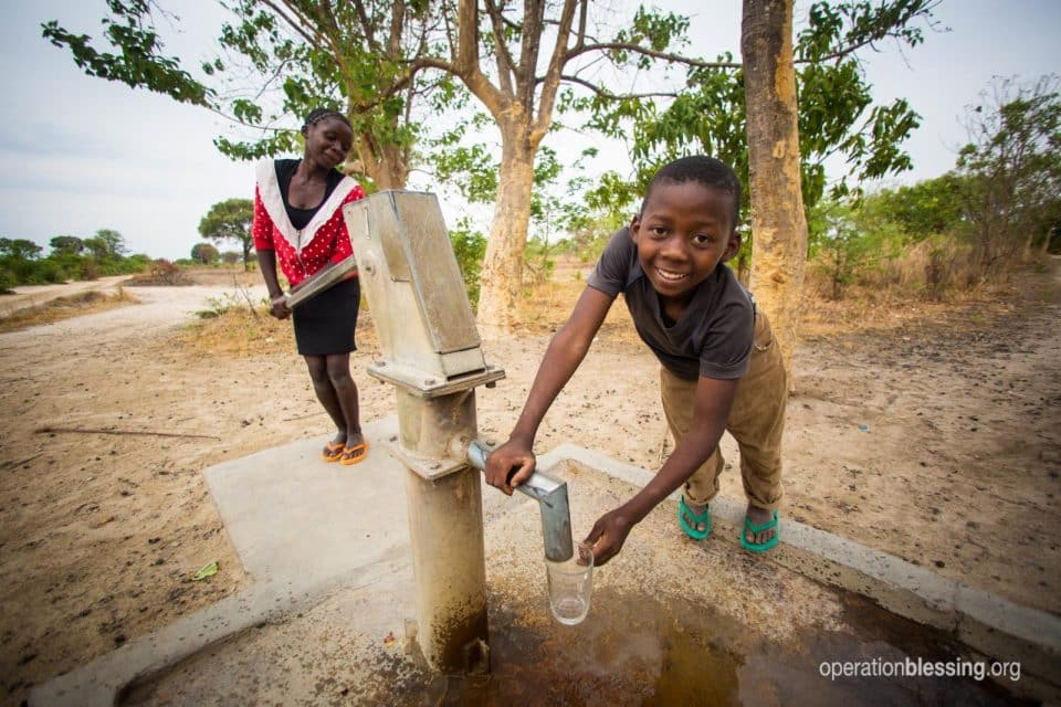 Children in Africa pump water from a clean water well.