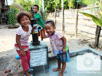 Asian children play by a safe water well from Operation Blessing partners.