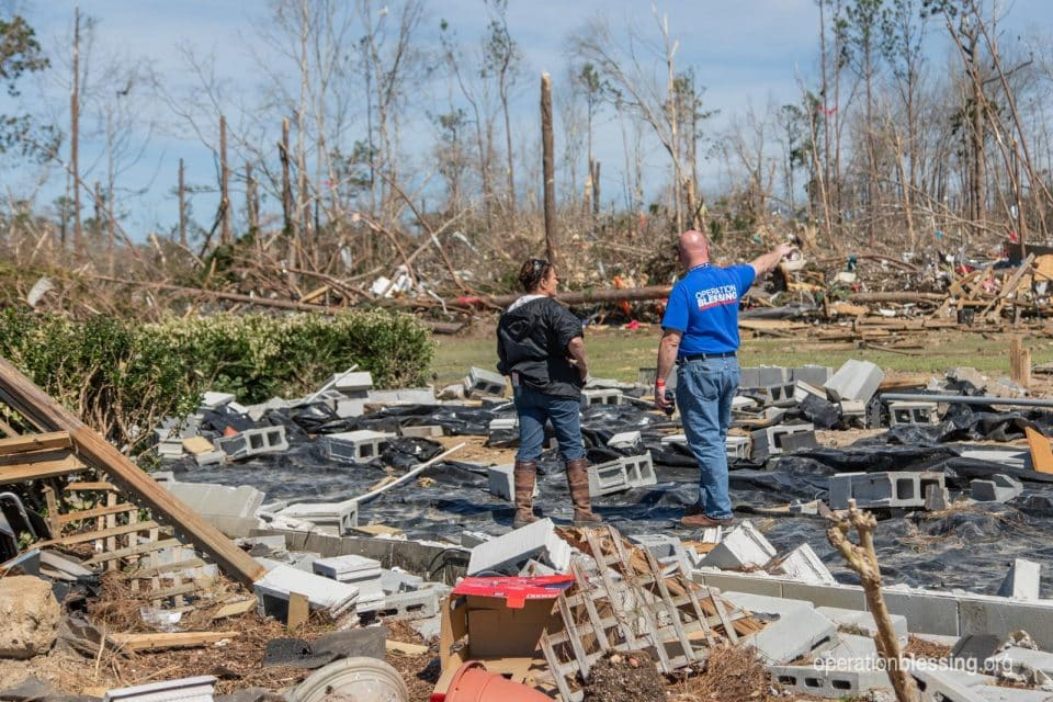 Operation Blessing worker providing tornado relief to a woman amid devastation.