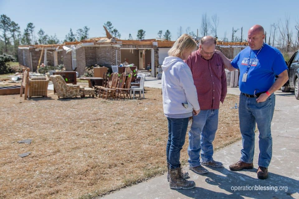 Operation Blessing worker encourages Tracy and Tommy as they receive tornado relief.