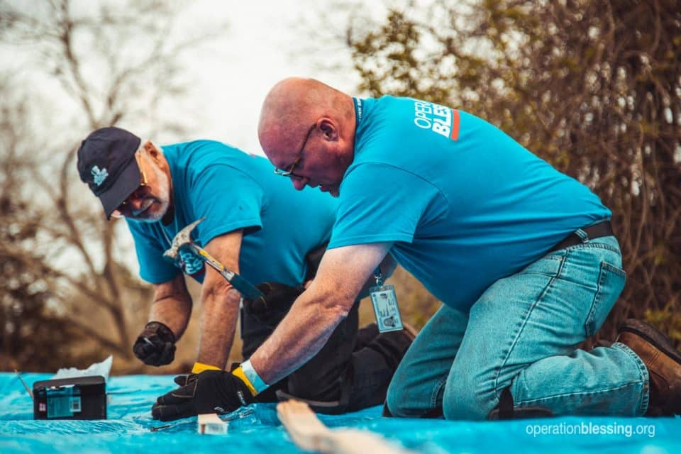 Operation blessing workers provide tornado relief by tarping a roof.