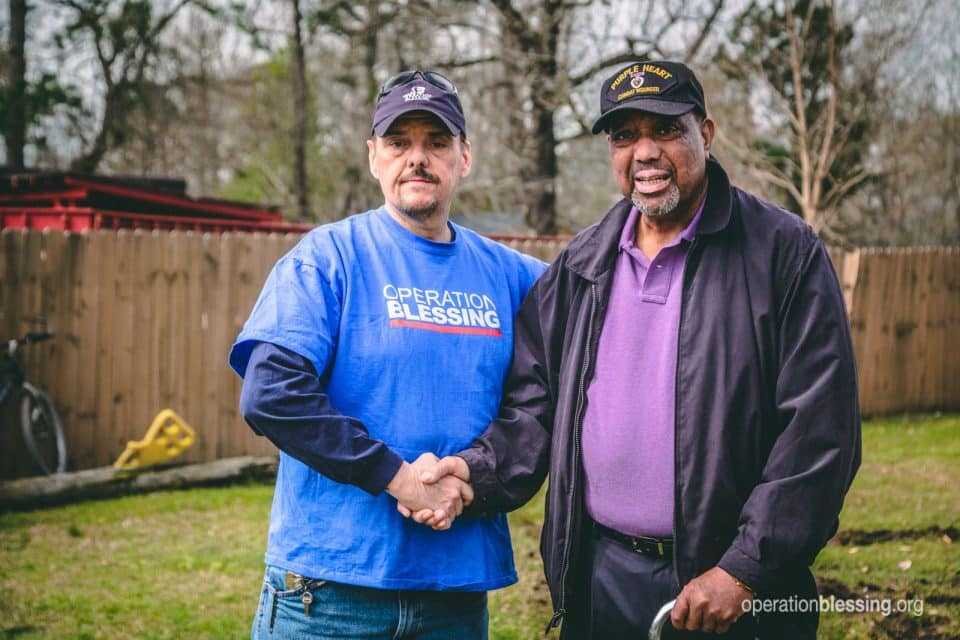Operation Blessing worker shaking the hand of Purple Heart veteran, Rudy.