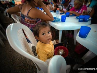 A young refugee from the Venezuela humanitarian crisis eats a meal.