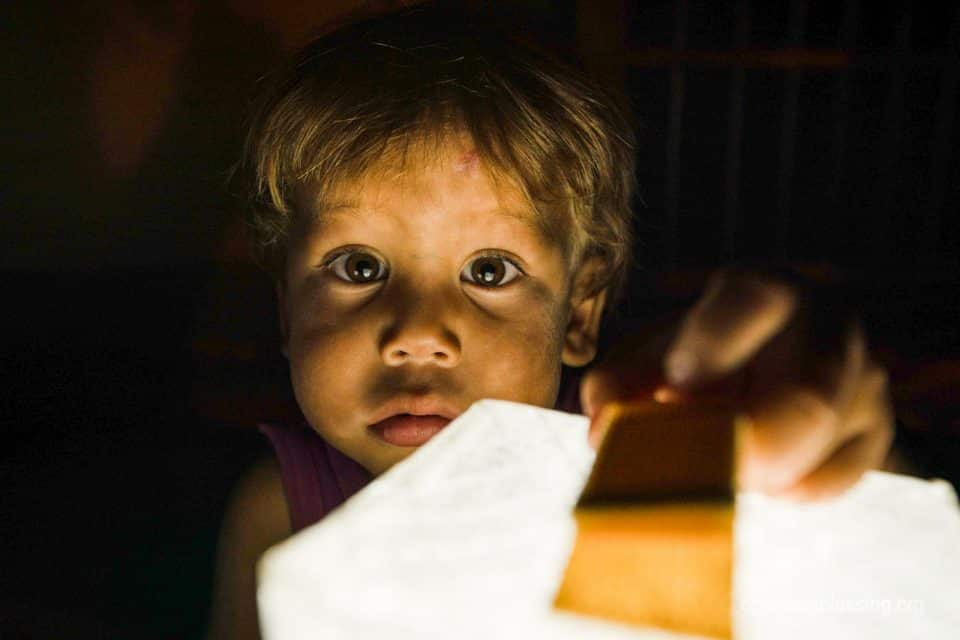 Venezuelan refugee child holding Operation Blessing solar light.