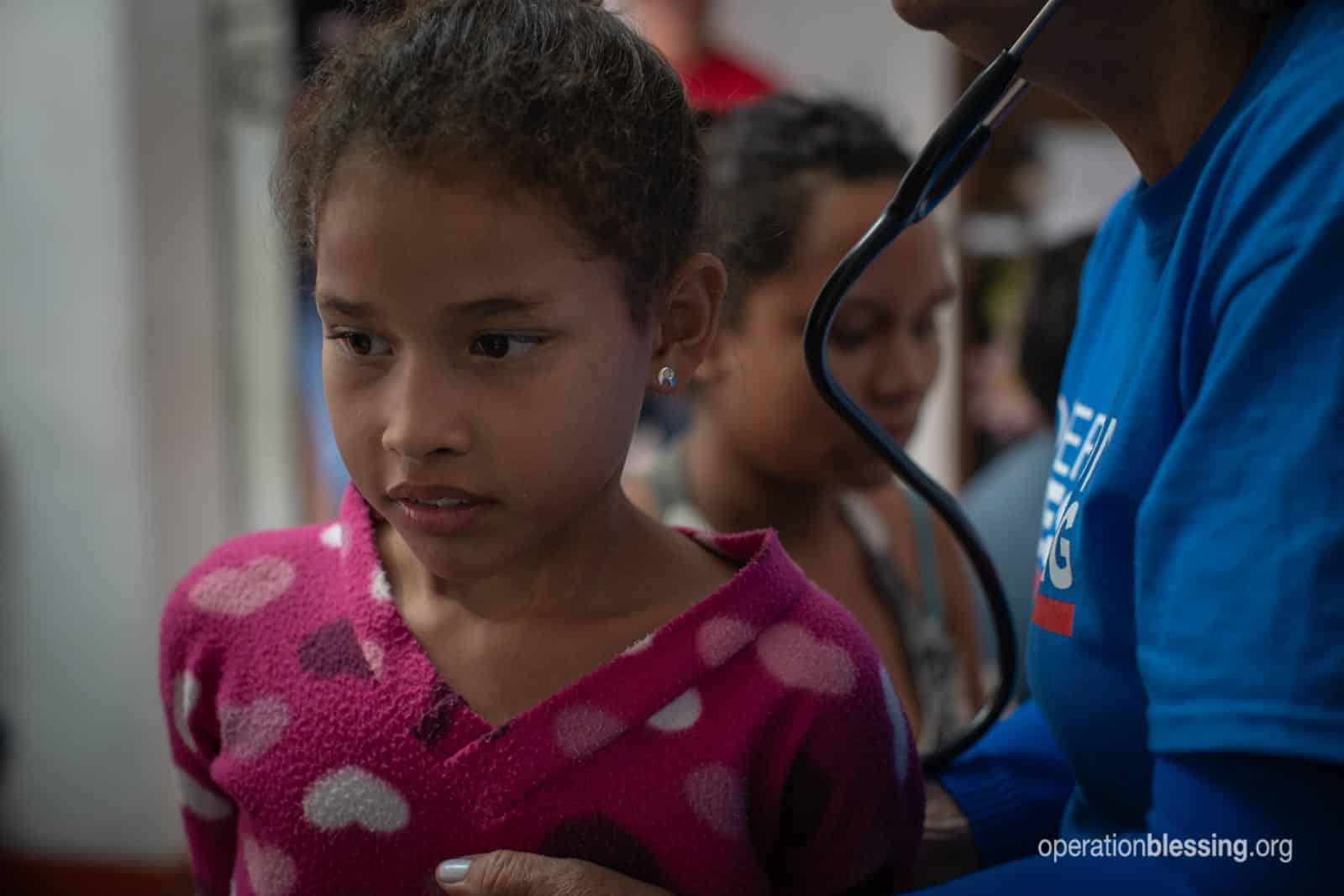 An Operation Blessing doctor checks a young girl near the Guatemalan border.