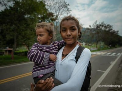 This mother and baby standing near the highway are Venezuelan refugees fleeing to Colombia.
