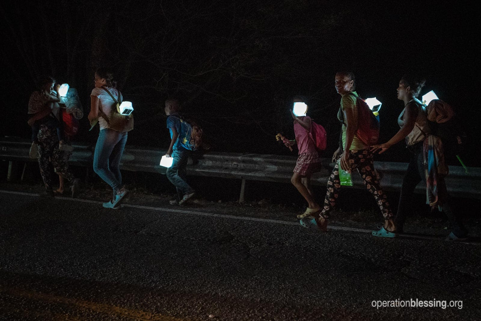 Venezuelan refugees walk on a highway in the dark with solar lamps from Operation Blessing.