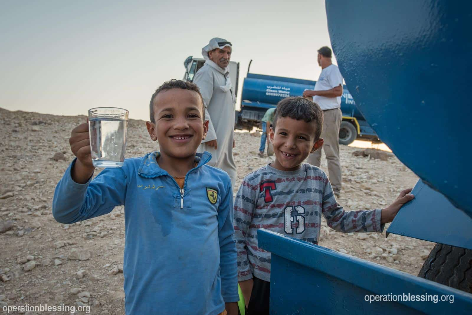 Celebrating World Water Day. Two boys in the Judean Desert with clean water.