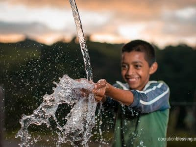 A boy splashing in fresh, clean water.
