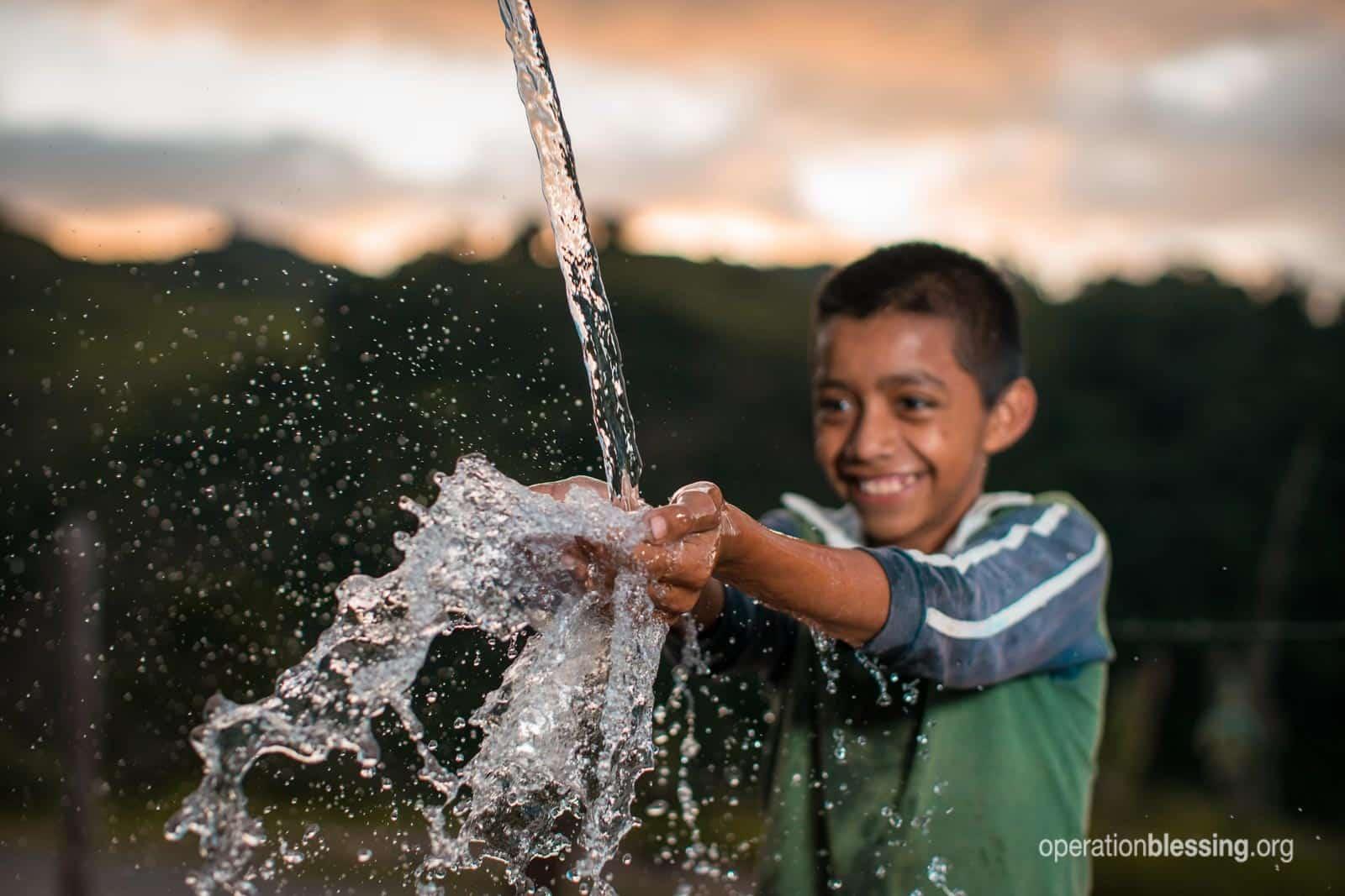 A boy splashing in fresh, clean water.