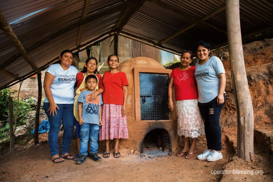 The pottery artisans of Juana's village stand in front of their new, safe kiln.