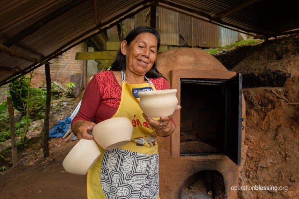 Juana holding her beautiful pottery.