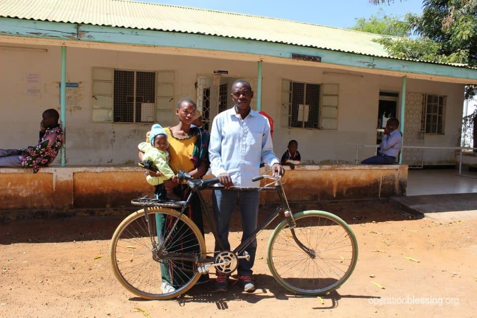 Vicent and his parents stand with the bike they rode to his clubfoot treatments.