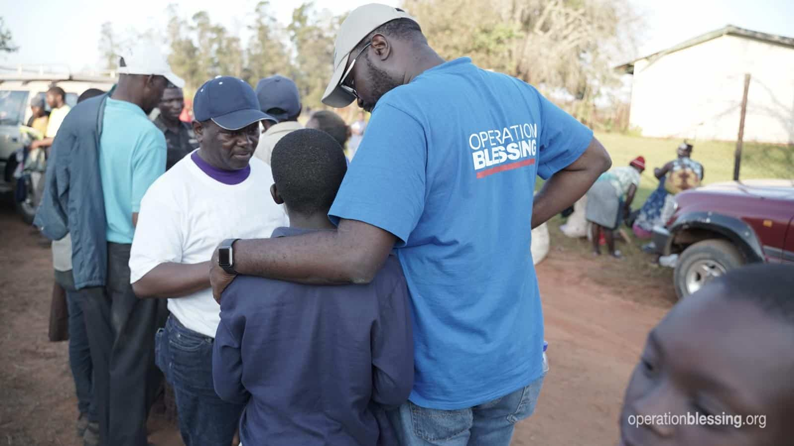 OB Kenya Director, Peter Kimaru, with his arm around a young boy from the camp, cyclone victim