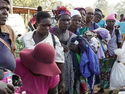 Women in camp line up for supplies after Cyclone Idai