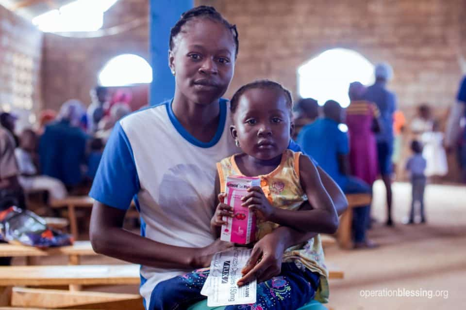 A Haitian mother and child receive medicine at an Operation Blessing medical brigade.