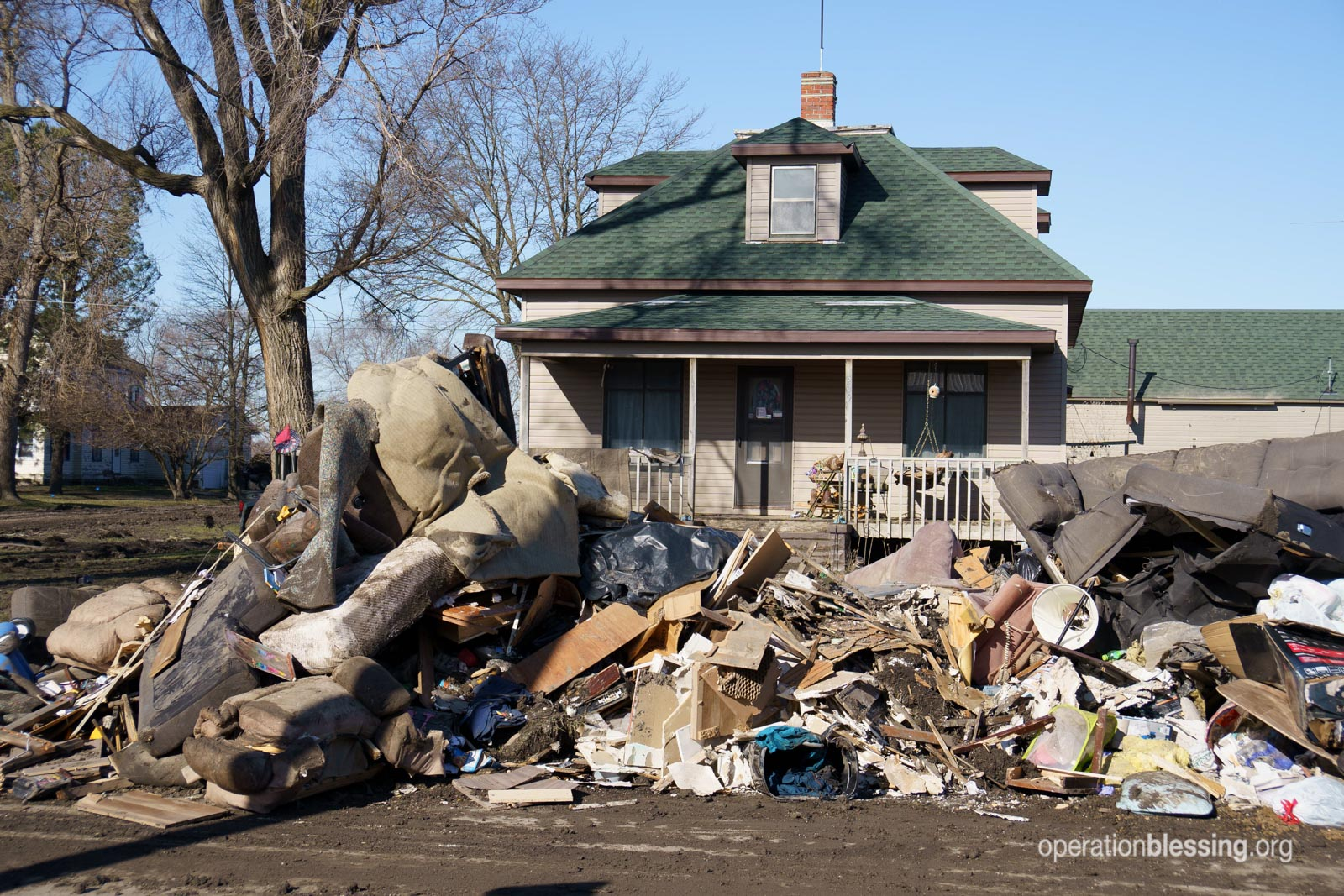 Debris in front of a flooded home in Nebraska