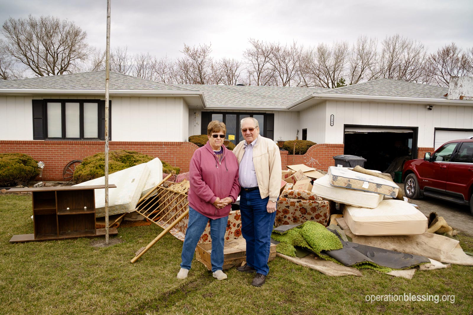 After floods in Nebraska, Linda and her husband, Ralph, stand in front of a pile of flood-soaked belongings.