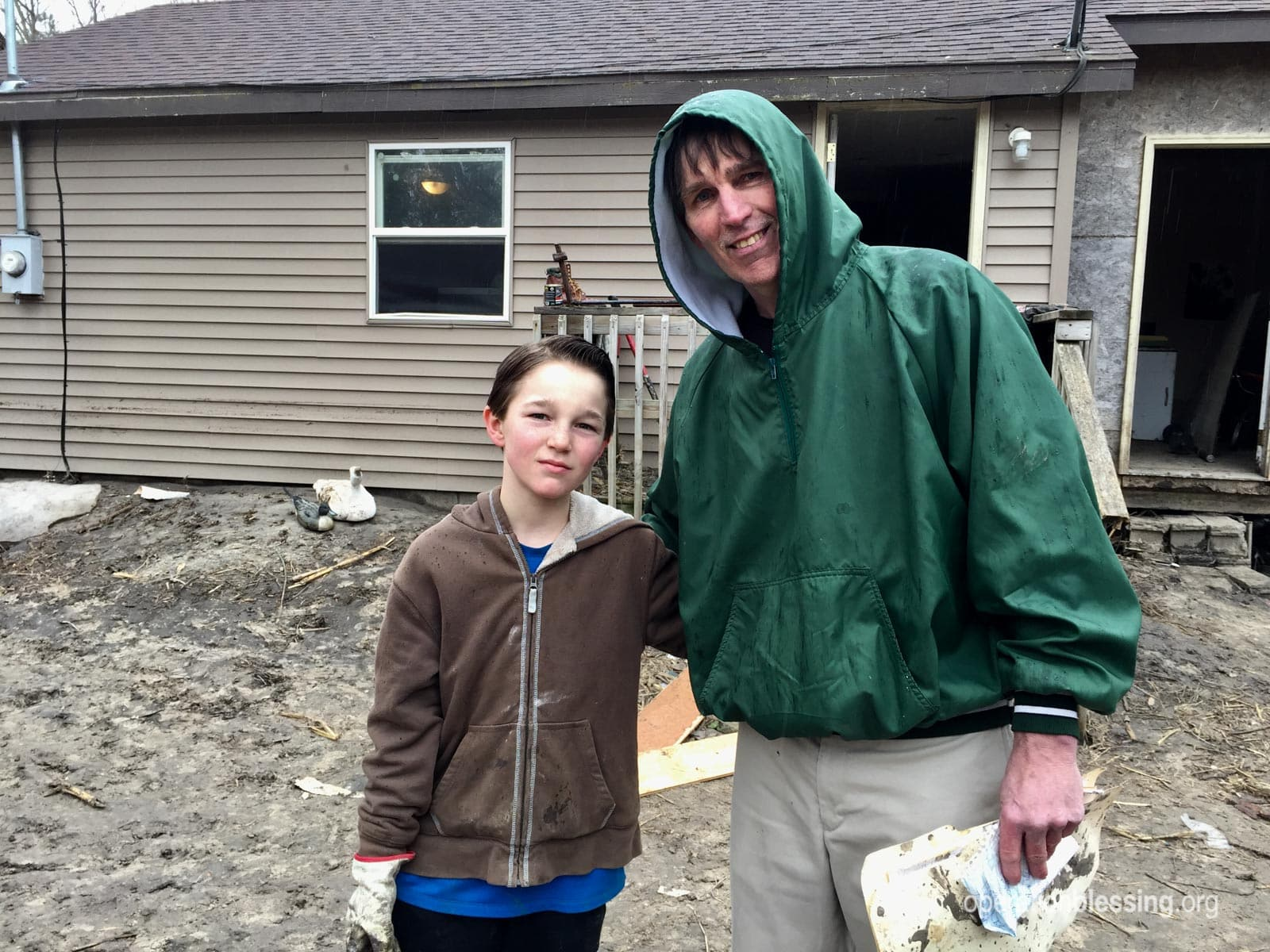 Jack and his son, TJ, stand in front of their flooded home in Nebraska.