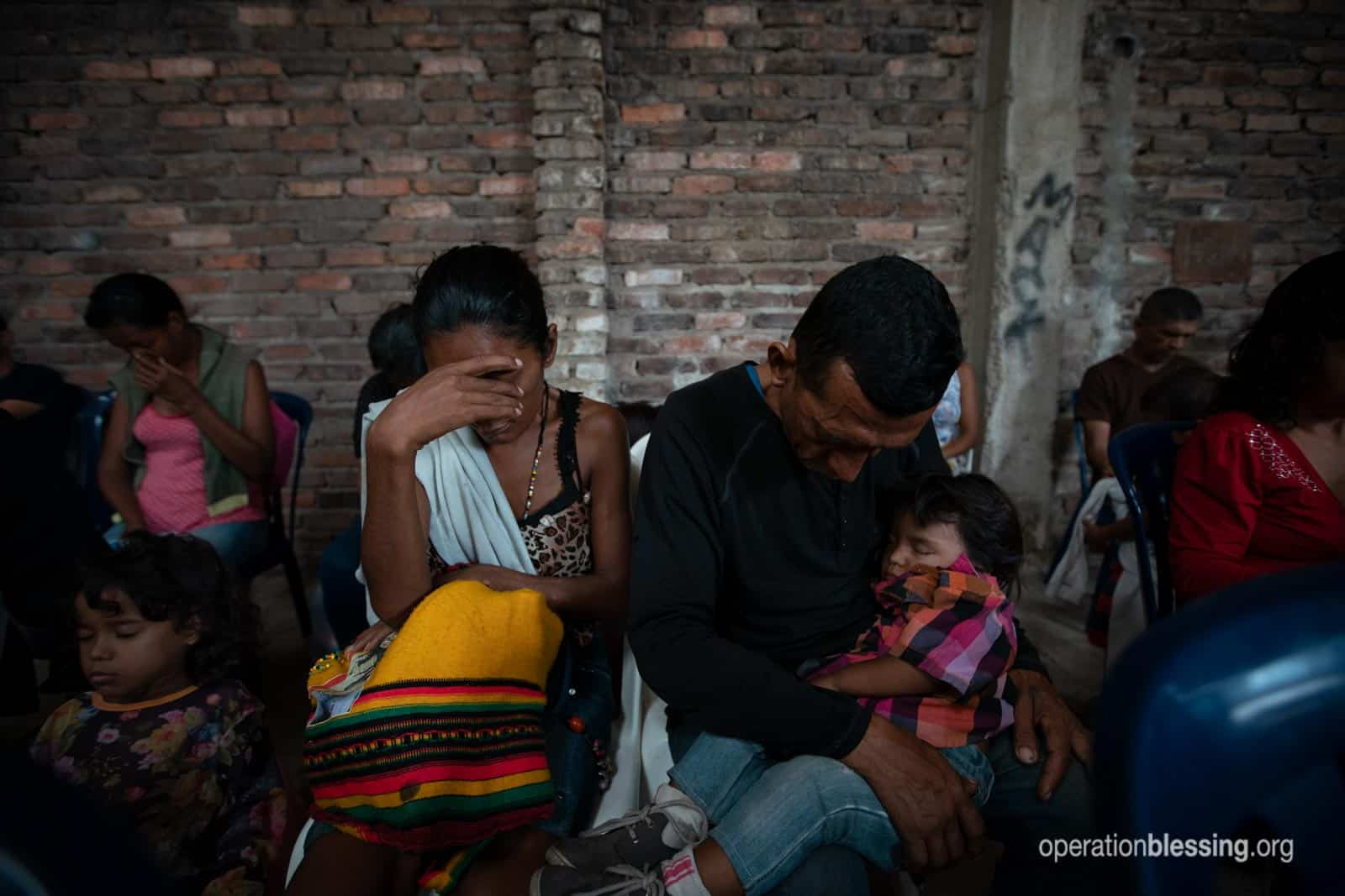 Desperate Venezuelan refugees look exhausted as they hold their child.