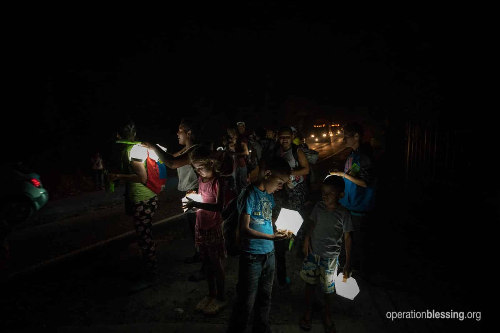 Venenzuelan refugees receive solar lights from Operation Blessing along a dangerous road.