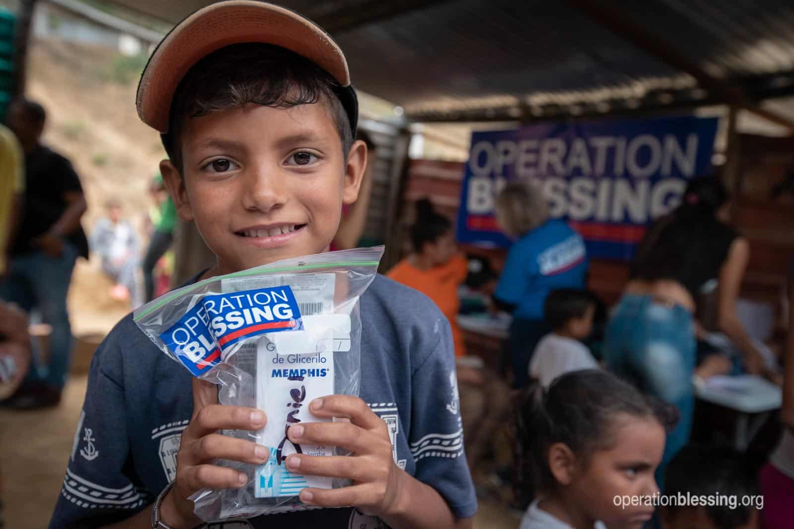 One of the young Venezuela refugees hold up a bag of free medications from Operation Blessing.