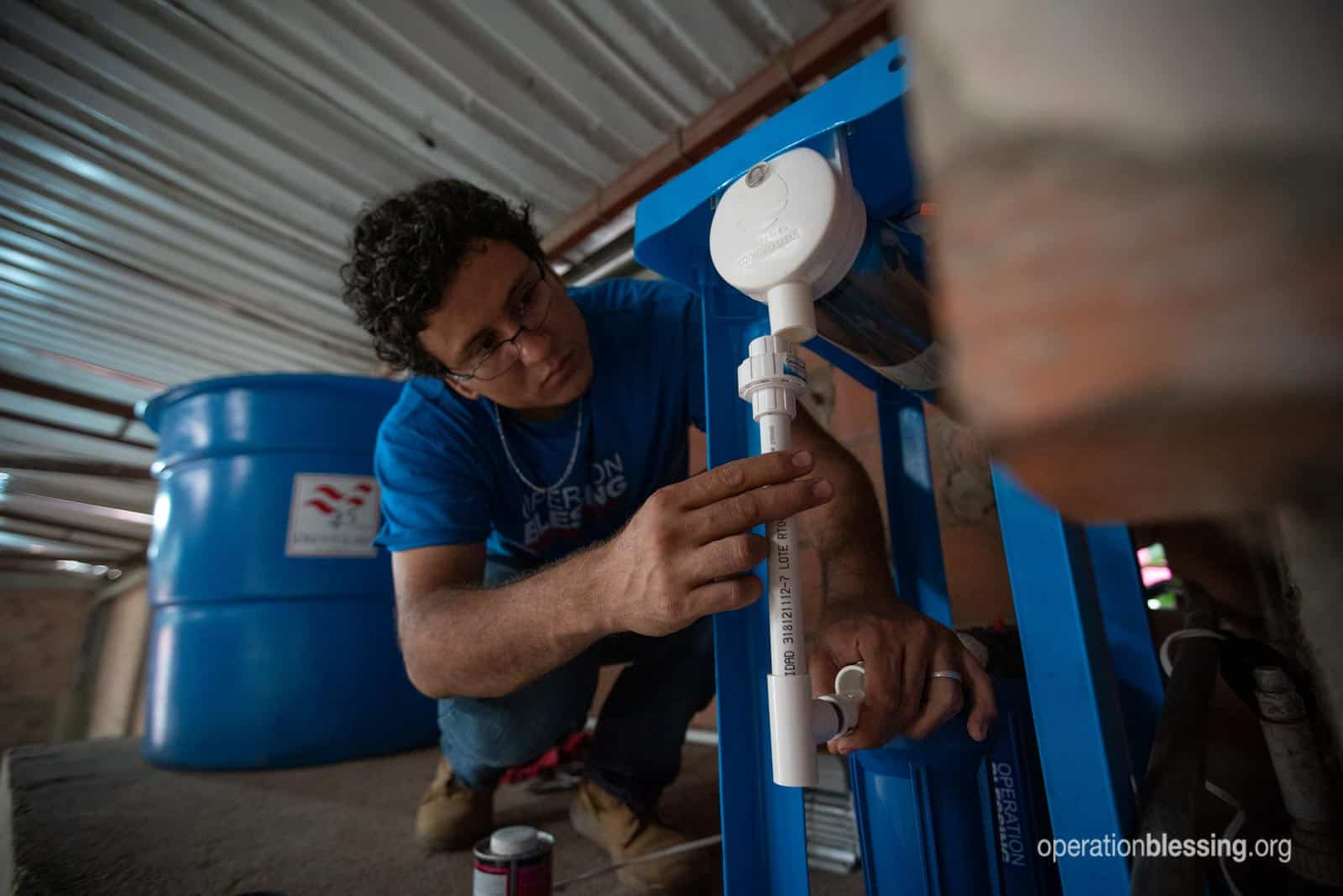 An Operation Blessing worker installs a safe water system for Venezuelan refugees.