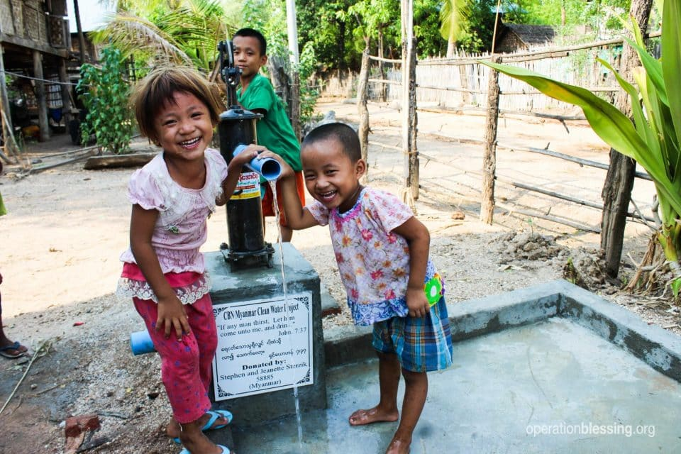 Children smile as they pump safe water from new water wells.