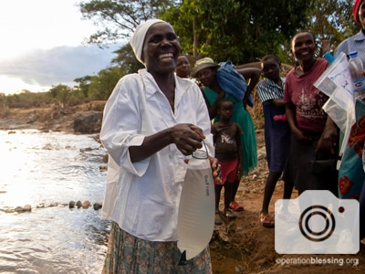 A smiling woman holds a water filer in Zimbabwe that will provide clean water after Cyclone Idai.