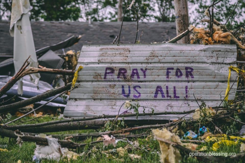 "A sign in the war zone rubble of the Dayton Tornado saying, ""Pray for us all."""