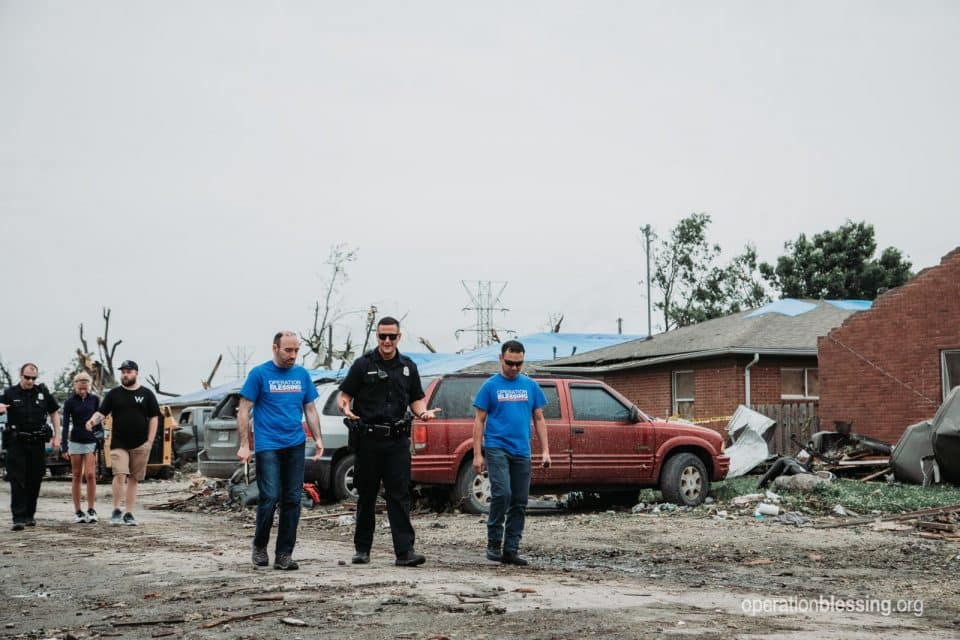 "Operation Blessing disaster relief workers walk with police through the ""war zone"" of Dayton, Ohio after a tornado."