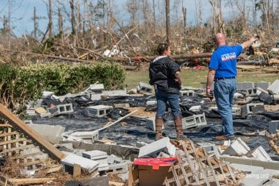An Operation Blessing worker helps a tornado victim. A disaster preparedness kit is helpful in these situations.