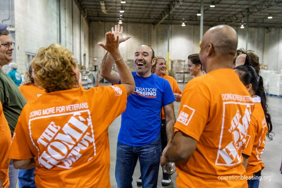 High fives between Operation Blessing and Home Depot volunteers