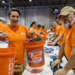 Home Depot volunteer holds up a disaster relief bucket, prepared with Operation Blessing for flood and hurricane victims.
